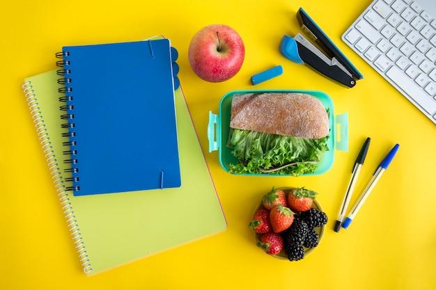 Cadernos, lancheira e papelaria na mesa