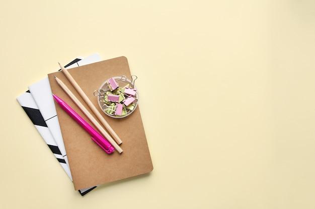 Cadernos, lápis, caneta, ligantes em fundo de biege. vista superior em vários artigos de papelaria na mesa.
