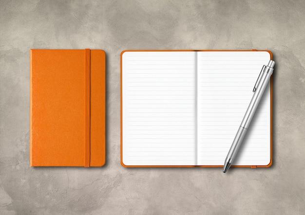Cadernos laranja fechados e abertos com uma caneta