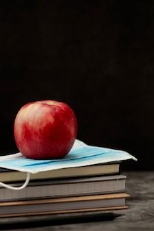 Cadernos, maçã vermelha e máscara médica de proteção facial