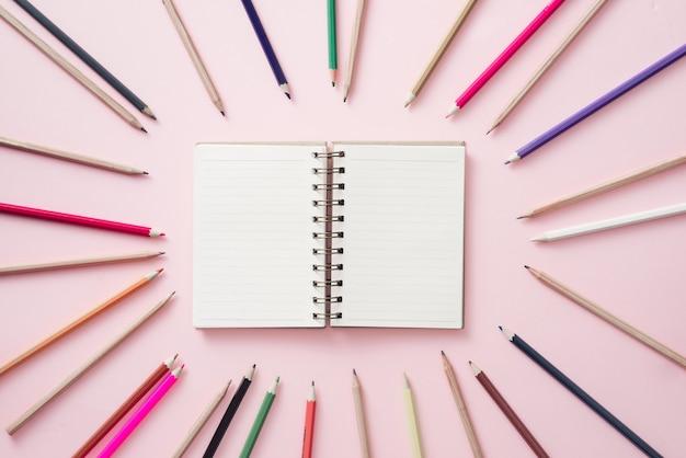 Cadernos no centro com lápis coloridos brilhantes alinhados ao redor do perímetro do fundo rosa.