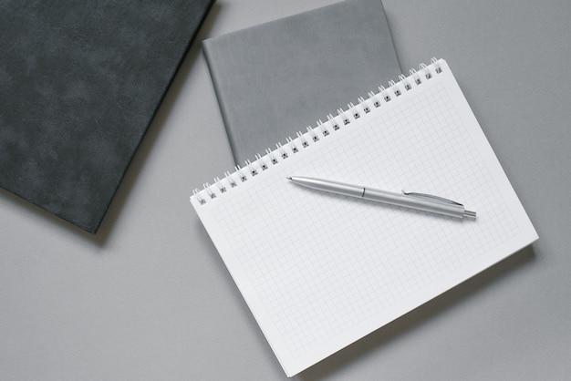 Cadernos ou diários com uma página em branco e uma caneta esferográfica em cima.