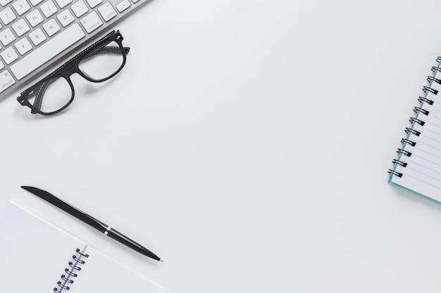 Cadernos perto de óculos e teclado