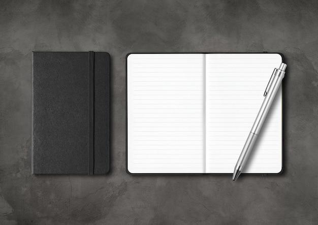Cadernos pretos com forro fechado e aberto com uma caneta. isolado em concreto escuro