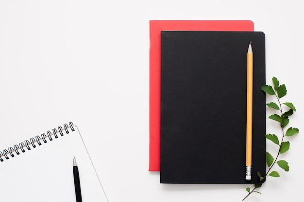 Cadernos pretos e vermelhos com um aberto