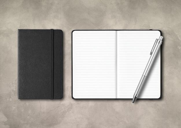 Cadernos pretos fechados e abertos com uma caneta isolada