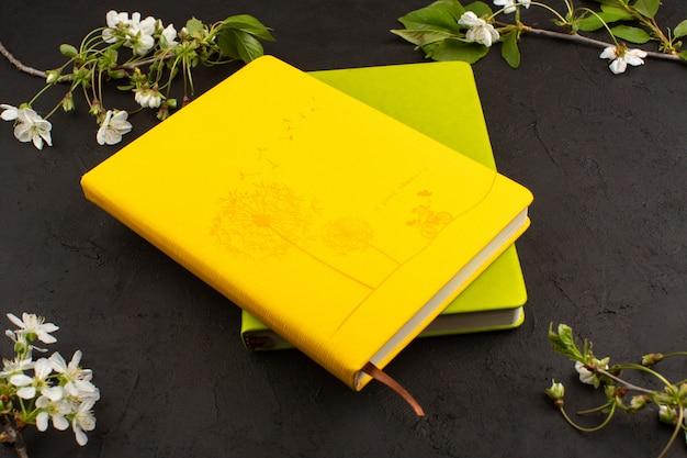 Cadernos verdes amarelos de vista superior, juntamente com flores brancas sobre o fundo escuro