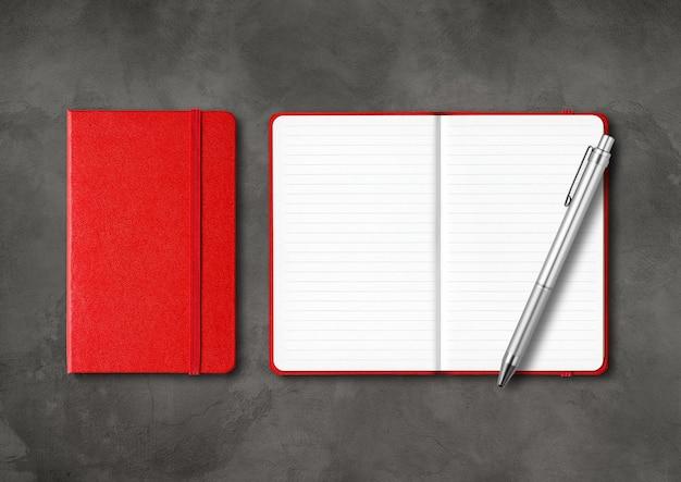 Cadernos vermelhos alinhados e fechados com uma caneta. maquete isolada em fundo escuro de concreto