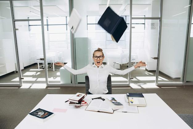 Cadernos voam sobre uma garota em óculos trabalhando na biblioteca