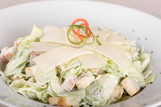 Caeser salad com filé de frango, chapa branca, fundo marrom