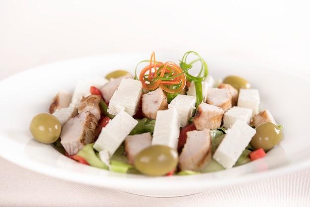Caeser salad com filé de frango, prato branco