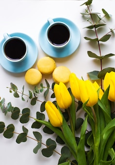 Café acabado de fazer, macarons e buquê de tulipas amarelas