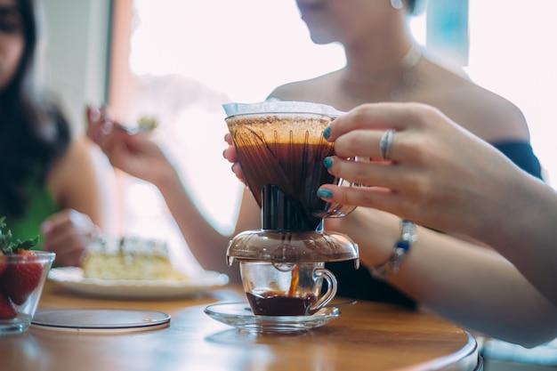 Café acabado de fazer na mesa com equipamento de filtro com café moído. cafeteria