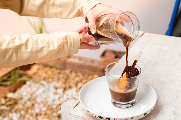 Café affogato com sorvete de chocolate em copo de vidro com fundo de jardim, coquetel de verão (close-up, foco seletivo)