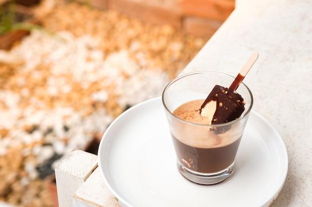 Café affogato com sorvete de chocolate pop em um copo de vidro com fundo de jardim.