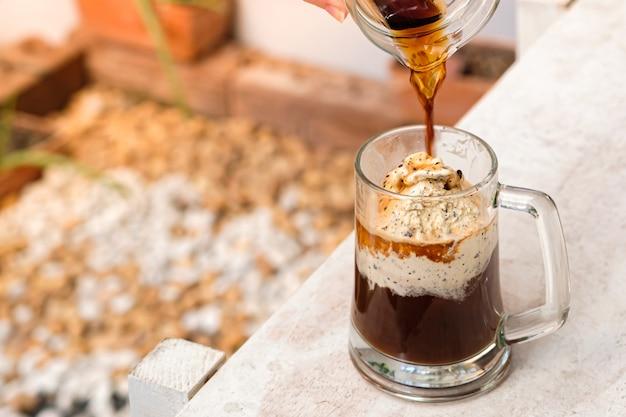 Café affogato com sorvete em um copo de vidro com fundo de jardim.
