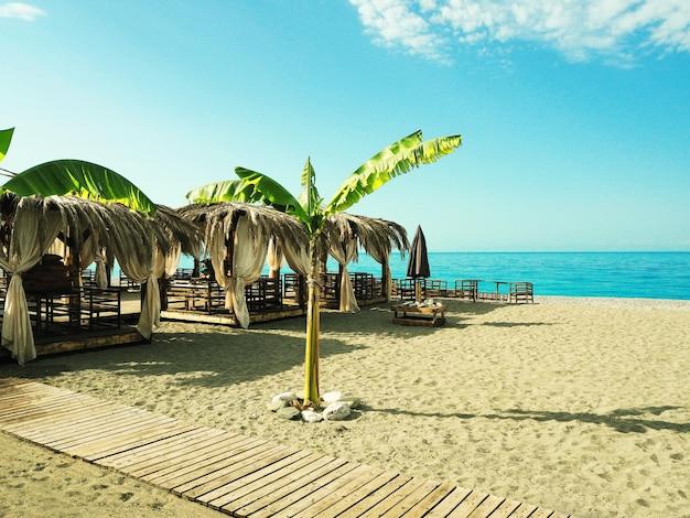 Café ao ar livre com mesas de madeira e telhado de palmeira no fundo do mar e do céu azul