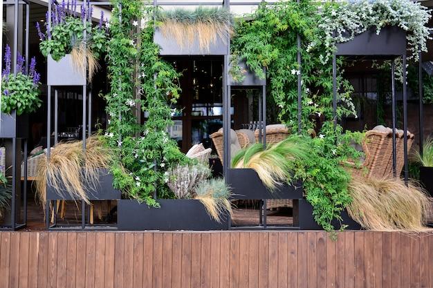 Café ao ar livre com móveis de vime e jardinagem vertical.