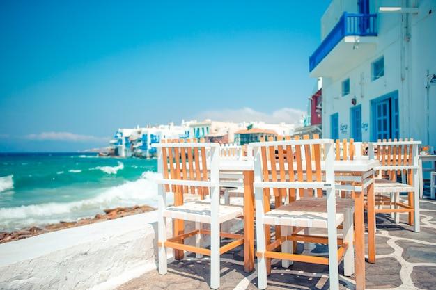 Café ao ar livre em uma rua da vila tradicional grega típica na grécia.