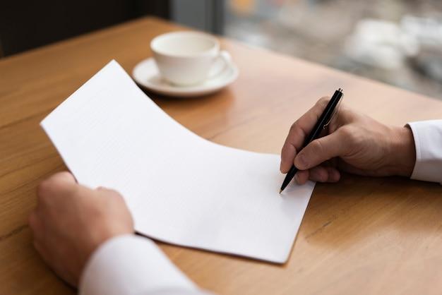 Café ao lado do homem irreconhecível escrevendo