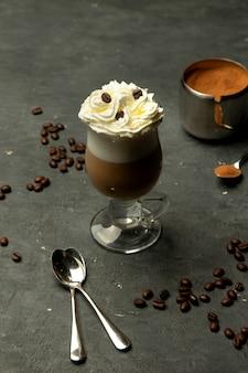 Café aromático em um copo de vidro com chantilly