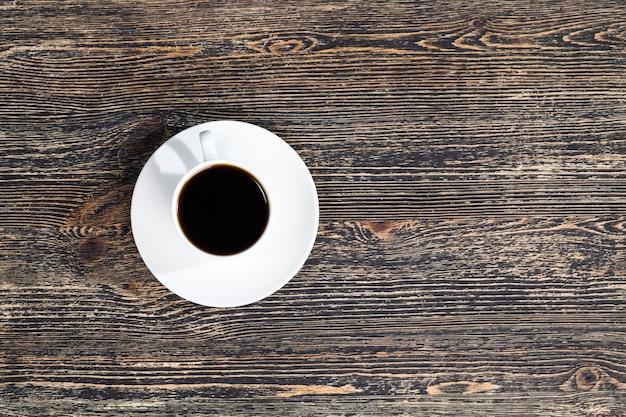 Café aromático em uma xícara branca durante uma refeição, café quente em uma caneca redonda, vista de cima closeup