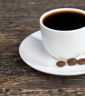 Café aromático em uma xícara branca durante uma refeição, café quente em uma caneca redonda, vista lateral com grãos de café torrados frescos, closeup