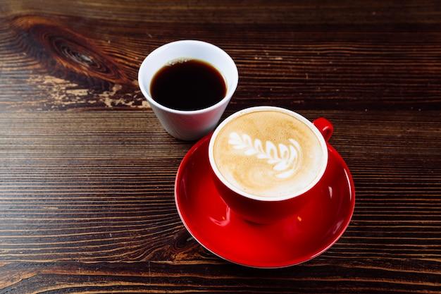 Café aromático em uma xícara vermelha com espuma de leite e latte art e café acabado de moer em uma xícara branca sobre uma mesa de madeira escura. a escolha do café.
