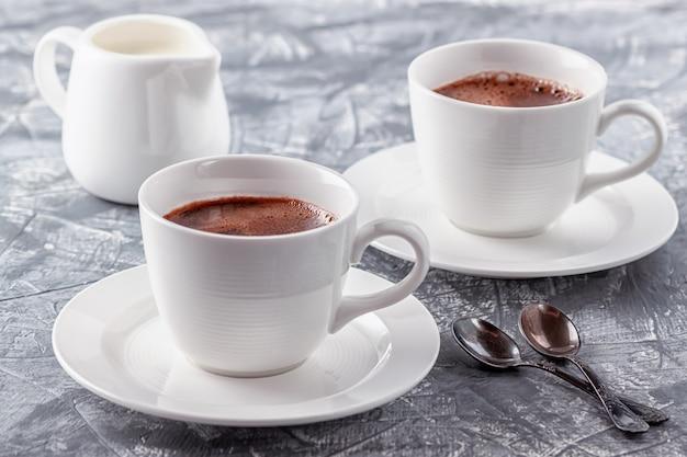 Café aromático fresco com creme em um cinza
