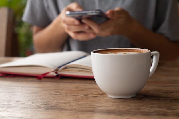 Café atrasado em um copo na frente - no projeto de conceito de trabalho em linha da tabela de madeira.
