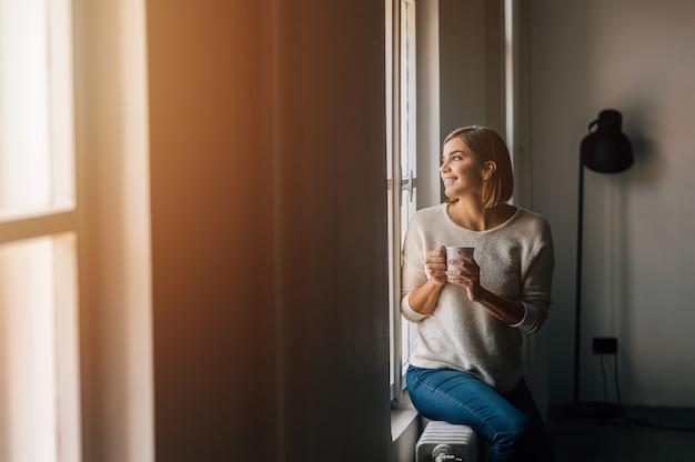 Café bebendo da jovem mulher bonita e vista através da janela ao sentar-se na soleira em casa.