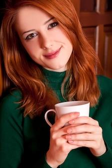Café bebendo da menina do ruivo do estilo perto das portas de madeira.