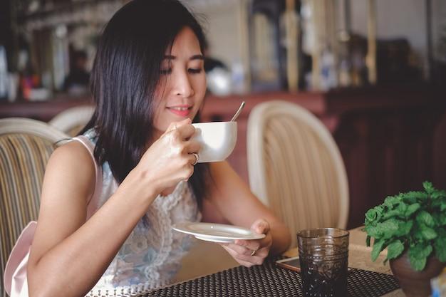 Café bebendo da mulher bonita de ásia na cafetaria no feriado.