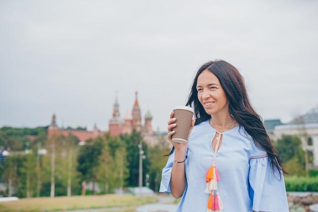 Café bebendo da mulher urbana nova feliz na cidade europeia.
