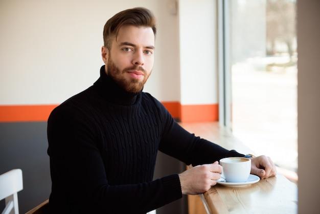 Café bebendo do homem de negócios novo bem sucedido atrativo que senta-se na tabela do café.