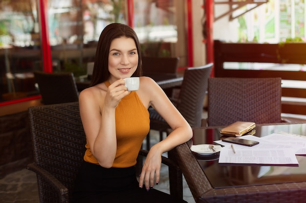 Café bebendo feliz da mulher de negócio com papéis dispersados na tabela. boas notícias, alegria e felicidade.