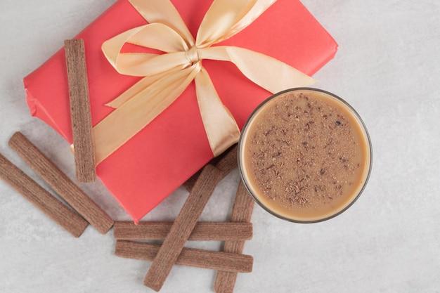 Café, biscoitos e caixa para presente em superfície de mármore
