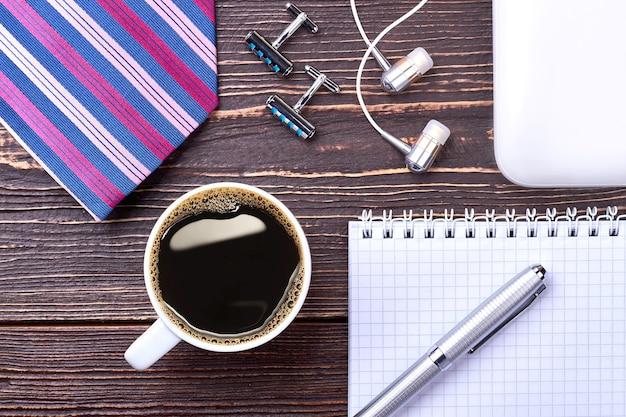 Café, caderno e caneta. fones de ouvido e botões de punho em madeira. estilo de manhã.