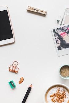 Café cappuccino; celular; prendedor de roupa; apontador; lápis; foto polaroid e celular no fundo branco