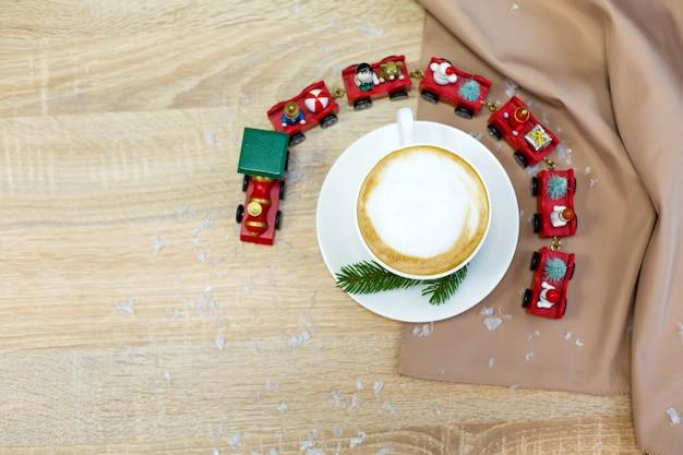 Café cappuccino de manhã festivo fresco delicioso em um copo de cerâmico branco em cima da mesa de madeira com trem de natal decorativo, ornamentais vermelhos, vaga-lumes e ramos de abeto