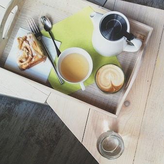 Café cappuccino e chá com pão de canela em um coffeeshop