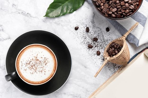 Café cappuccino quente com grãos de café moído na mesa de mármore