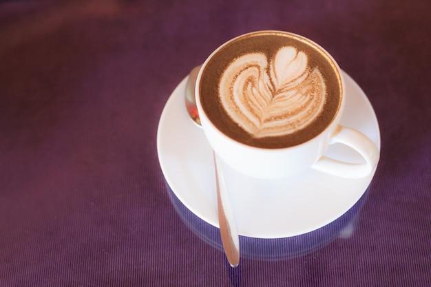 Café cappuccino quente decorado com arte de espuma de flor desabrochando em espuma de leite cozido no vapor