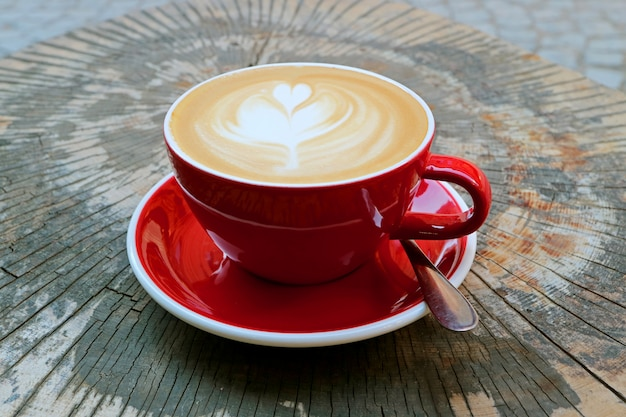 Café cappuccino quente no copo vermelho servido na mesa de tronco de árvore