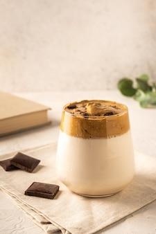 Café caseiro dalgona com chocolate no guardanapo na luz de fundo.