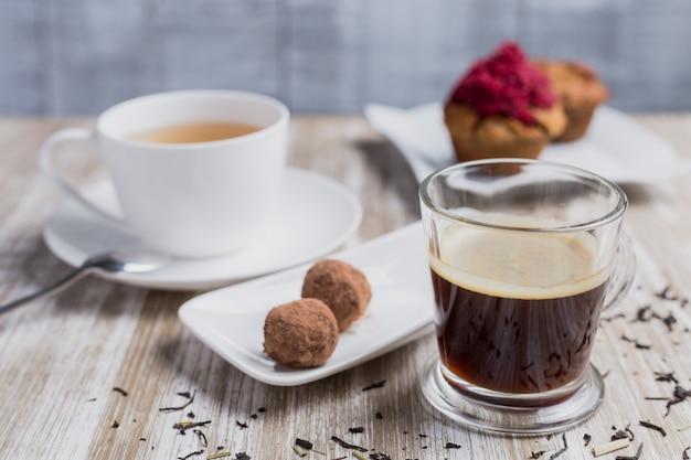 Café, chá, dois cupcakes e dois doces de coco