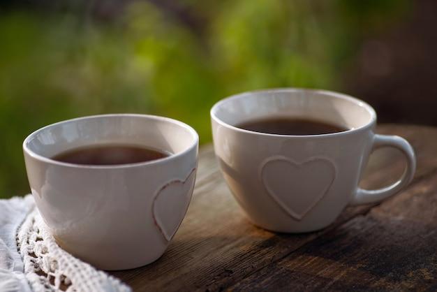 Café, chá em xícaras com decoração de coração, guardanapo de renda sobre uma mesa de madeira. refeições leves para brunch ao ar livre.