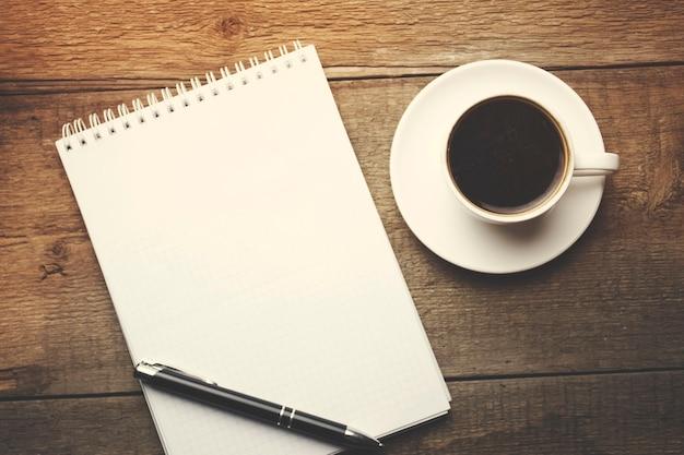 Café com caderno em branco e telefone na mesa de madeira