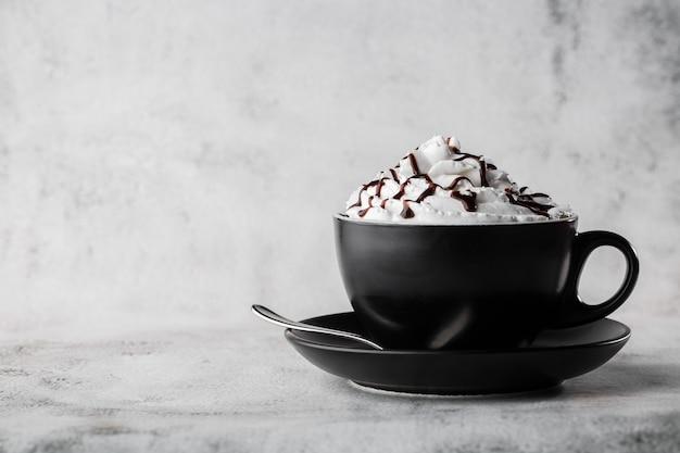 Café com chantilly e cobertura de chocolate. café gelado em copo escuro, isolado no fundo de mármore brilhante. visão aérea, copie o espaço. publicidade para o menu de café. menu de café. foto horizontal.