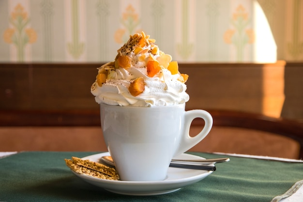 Café com chantilly e frutas secas em copo branco sobre a mesa de um café com um pequeno biscoito
